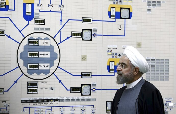 FILE - In this Jan. 13, 2015, file photo released by the Iranian President's Office, President Hassan Rouhani visits the Bushehr nuclear power plant just outside of Bushehr, Iran. Iran announced Tuesday it would inject uranium gas into 1,044 centrifuges it previously kept empty under its 2015 nuclear deal with world powers. (AP Photo/Iranian Presidency Office, Mohammad Berno, File)