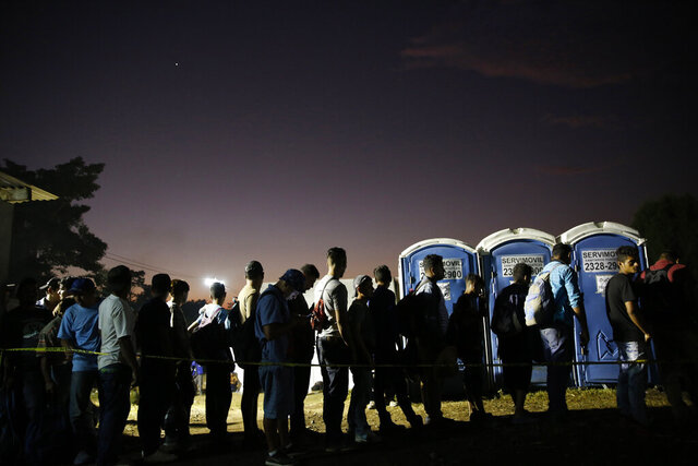 Central American migrants stand in line for food at a temporary shelter for migrants set up by authorities in Tecun Uman, Guatemala on the border with Mexico, Wednesday, Jan. 22, 2020, a location popular for migrants to cross from Guatemala to Mexico. (AP Photo/Moises Castillo)