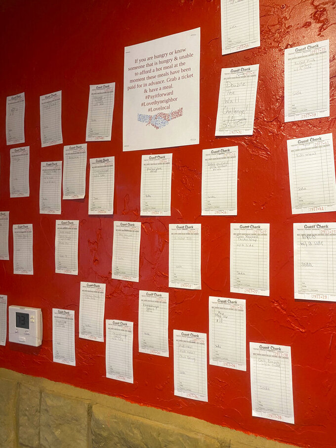 In this Feb. 11, 2021, photo provided by The Dawg House, receipts for pre-paid meals hang on the wall inside The Dawg House in Miami, Okla. Customers pay for them so that people in need, many of them struggling financially due to the coronavirus pandemic, can get a meal, judgment-free and no questions asked. (The Dawg House via AP)