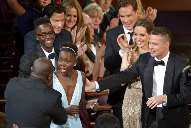 FILE - In this March 2, 2014 file photo, director Steve McQueen, left, congratulates Lupita Nyong'o on her win for best actress in a supporting role for