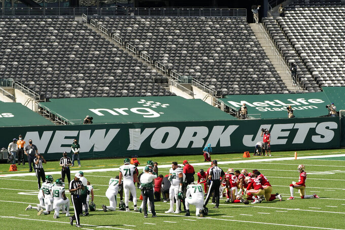 Players gather around an injured person during the first half of an NFL football game between the New York Jets and the San Francisco 49ers at a nearly empty MetLife Stadium, Sunday, Sept. 20, 2020, in East Rutherford, N.J. (AP Photo/Corey Sipkin)