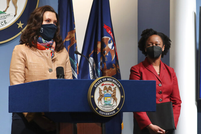 In this photo provided by the Michigan Office of the Governor, Gov. Gretchen Whitmer addresses the state as Michigan Department of Health and Human Services Chief Medical Executive Dr. Joneigh Khaldun, right, listens in on Friday, April 9, 2021, in Lansing, Mich. Faced with the country's highest rate of new coronavirus infections, Whitmer on Friday urged a two-week suspension of in-person high school classes, all youth sports and indoor restaurant dining. (Michigan Office of the Governor via AP)