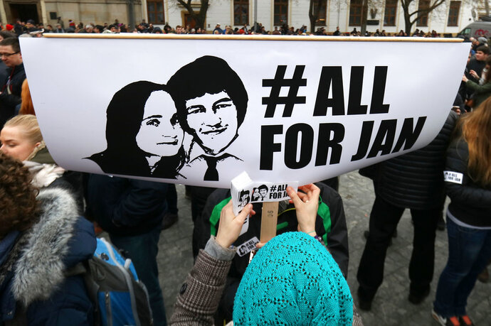 FILE- In this Friday, March 9, 2018, file picture a woman places a sticker on a poster with a photo of slain journalist Jan Kuciak during an anti-government rally in Bratislava, Slovakia. Tens of thousands of Slovaks have taken to the streets again on Sunday, April 15, 2018, in the continuing anti-government protests amid a political crisis triggered by the slayings of an investigative journalist and his fiancee with protesters demanding a thorough and independent investigation into the Feb. 21 shooting deaths and the dismissal of the national police chief, Tibor Gaspar, and Dusan Kovacik, a prosecutor who heads an special office dealing with corruption.(AP Photo/Ronald Zak, File)