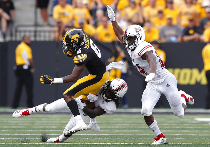 Iowa wide receiver Ihmir Smith-Marsette (6) runs from Northern Illinois defenders Tifonte Hunt, center, and Trequan Smith, right, after making a reception during the second half of an NCAA college football game, Saturday, Sept. 1, 2018, in Iowa City, Iowa. Iowa won 33-7. (AP Photo/Charlie Neibergall)
