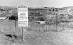 FILE - In this Nov. 13, 1979, file photo, while United Nuclear Corp. uses a combination of hand work and heavy machinery to clear up a uranium tailings spill along the Rio Puerco, signs warn residents in three languages to avoid the water in Church Rock, N.M. A bipartisan group of lawmakers is renewing the push to expand a federal compensation program for radiation exposure following uranium mining and nuclear testing carried out during the Cold War. Advocates have been trying for years to bring awareness to the lingering effects of nuclear fallout surrounding the Trinity Site in southern New Mexico and on the Navajo Nation, where more than 30 million tons of ore were extracted over decades to support U.S. nuclear activities. (AP Photo/SMH, File)