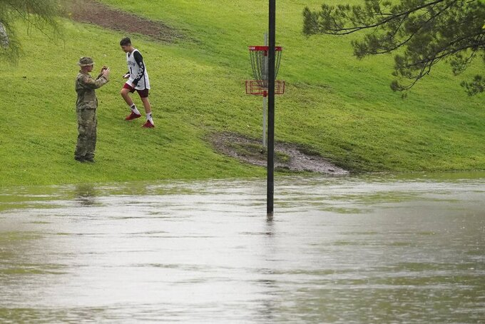 People check out the flooding at Vista del Camino Park as heavy rains come down, Friday, July 23, 2021, in Scottsdale, Ariz. (AP Photo/Ross D. Franklin)