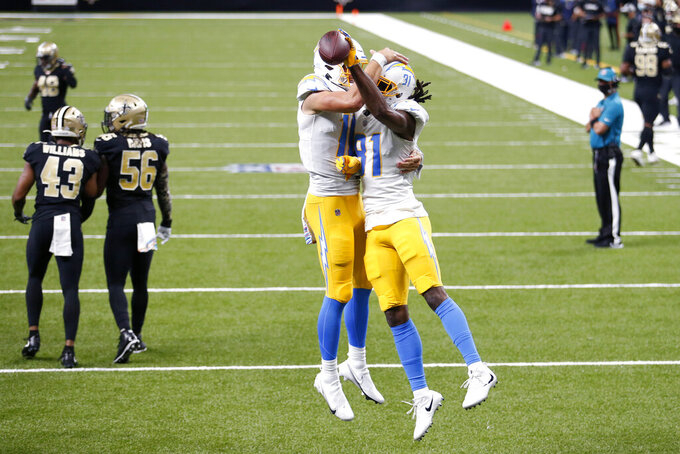 Los Angeles Chargers wide receiver Mike Williams (81) celebrates his touchdown reception with quarterback Justin Herbert as Los Angeles Chargers cornerback Michael Davis (43) and linebacker Kenneth Murray (56) walk away in the first half of an NFL football game in New Orleans, Monday, Oct. 12, 2020. (AP Photo/Brett Duke)