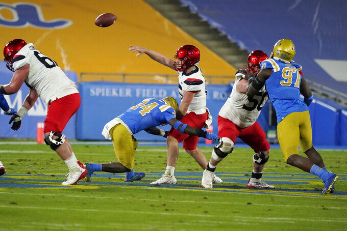 Arizona quarterback Will Plummer, center, throws under pressure during the first half of the team's NCAA college football game against UCLA on Saturday, Nov. 28, 2020, in Pasadena, Calif. (AP Photo/Marcio Jose Sanchez)