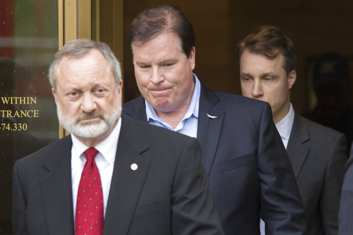 Stephen Calk, center, leaves Federal court with his attorney Jeremy Margolis, left, Thursday, May 23, 2019, in New York. Calk charged in New York with issuing loans to win a role in President Donald Trump's administration has pleaded not guilty. (AP Photo/Mary Altaffer)