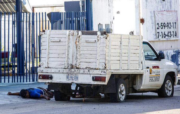 The bullet riddled bodies of two men lie on the ground next to a vehicle, a day after a gun battle between gunmen and security forces in Culiacan, Mexico, Friday Oct. 18, 2019. Mexican officials say eight people were killed in the battles in what is being described as a failed operation to detain the son of convicted Sinaloa cartel boss Joaquin