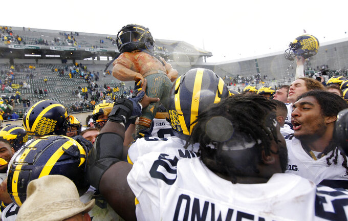 Michigan players celebrate with the Paul Bunyan trophy following their 21-7 win over Michigan State in an NCAA college football game, Saturday, Oct. 20, 2018, in East Lansing, Mich. (AP Photo/Al Goldis)