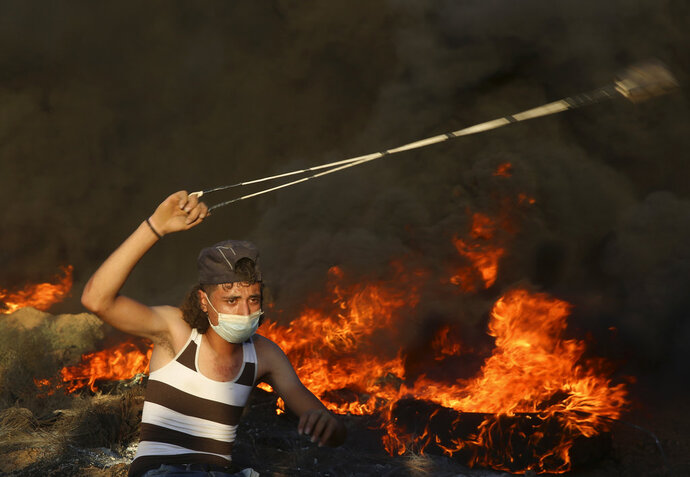 A protester hurls stones while others burn tires near the fence of the Gaza Strip border with Israel, during a protest east of Gaza City, Friday, Sept. 14, 2018. Gaza health officials say 3 Palestinians, including 12-year-old boy, were killed by Israeli army fire in protests along Gaza's perimeter fence. (AP Photo/Adel Hana)