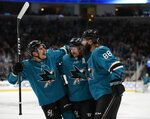 From left to right, San Jose Sharks right wing Timo Meier (28) and defenseman Erik Karlsson (65) celebrate with defenseman Brent Burns (88) who scored a goal against the Dallas Stars during the first period of an NHL hockey game in San Jose, Calif., Saturday, Jan. 11, 2020. (AP Photo/Josie Lepe)