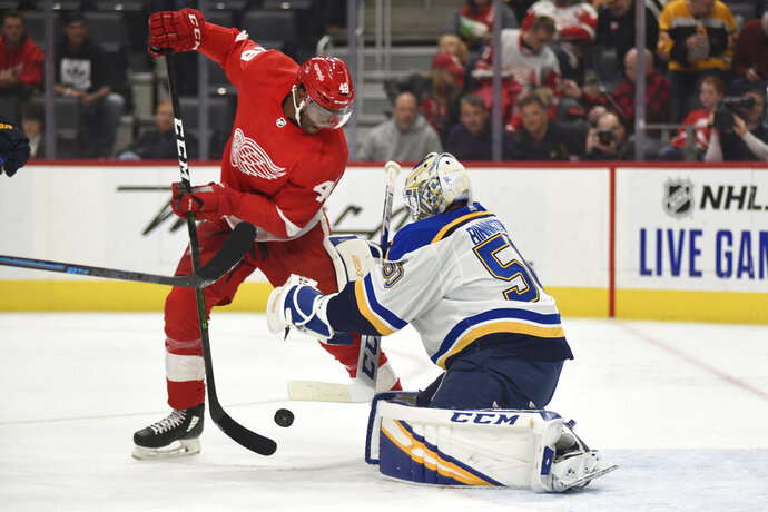 Detroit Red Wings right wing Givani Smith, left, has the puck knocked away by St. Louis Blues goaltender Jordan Binnington in the second period of an NHL hockey game, Sunday, Oct. 27, 2019. (AP Photo/Jose Juarez)