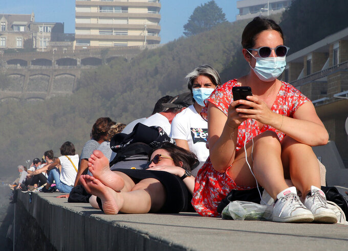 People sunbathe near the Atlantic ocean in Biarritz, southwestern France, Sunday, Nov. 1, 2020. People from Biarritz bathe in the Atlantic Ocean to protest against the ban on access to the ocean for the entire population because of the latest nationwide lockdown as France re-imposed a monthlong nationwide lockdown Friday aimed at slowing the spread of the coronavirus. (AP Photo/Bob Edme)