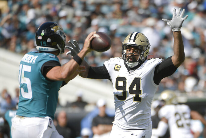 New Orleans Saints defensive end Cameron Jordan (94) tries to block a pass by Jacksonville Jaguars quarterback Gardner Minshew, left, during the second half of an NFL football game, Sunday, Oct. 13, 2019, in Jacksonville, Fla. (AP Photo/Phelan M. Ebenhack)