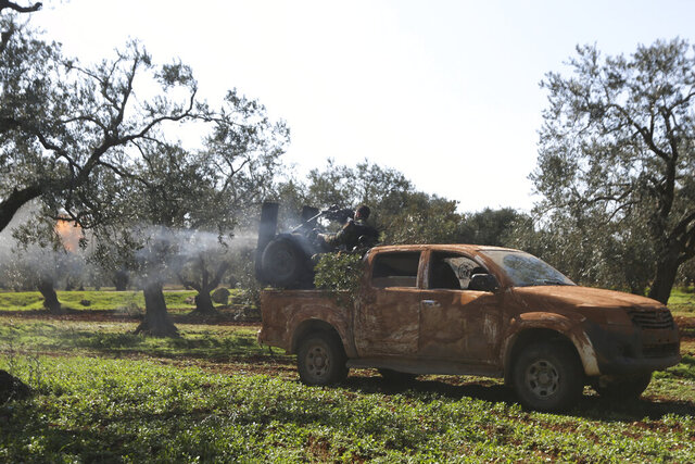 Turkish backed rebel fighters fire heavy machine gun near the village of Neirab in Idlib province, Syria, Thursday, Feb. 20, 2020. Two Turkish soldiers were killed Thursday by an airstrike in northwestern Syria, according to Turkey's Defense Ministry, following a large-scale attack by Ankara-backed opposition forces that targeted Syrian government troops. (AP Photo/Ghaith Alsayed)