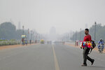 India's Presidential Palace, in the backdrop, is covered with smog as as a roadside vendor crosses Rajapth, the ceremonial boulevard in New Delhi, India, Wednesday, Oct. 16, 2019. The Indian capital's air quality levels have plunged to