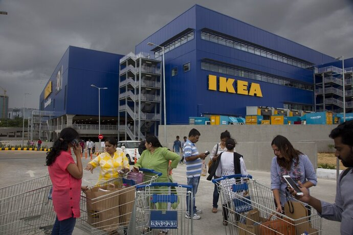 FILE- In this Aug. 9, 2018, file photo, Customers stand outside Ikea's first store in India as it opened in Hyderabad, India. India is a test case for whether Ikea should keep shifting resources toward emerging economies, including Latin America and China, given the saturation of markets in Europe and the United States, and the possibility of another global recession. Six months after Ikea opened its first store in Hyderabad, the 400,000-square-foot cornucopia of furniture, linens, kitchenware and other goodies is drawing between 10,000 and 30,000 visitors per day. (AP Photo/Mahesh Kumar A, File)