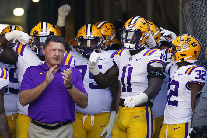 LSU coach Ed Orgeron, left, prepares to lead his team onto the field before an NCAA college football game against UCLA on Saturday, Sept. 4, 2021, in Pasadena, Calif. (AP Photo/Marcio Jose Sanchez)