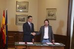 Spain's caretaker Prime Minister Pedro Sanchez, left, and Podemos party leader Pablo Iglesias shake hands after signing an agreement at the parliament in Madrid, Spain, Tuesday, Nov. 12, 2019. The leaders of Spain's Socialist party and the left-wing United We Can (Podemos) party say they have reached a preliminary agreement toward forming a coalition government. But the deal announced Tuesday won't provide enough votes in parliament for the Socialists, who won a general election, to take office without the support of other parties. (AP Photo/Paul White)