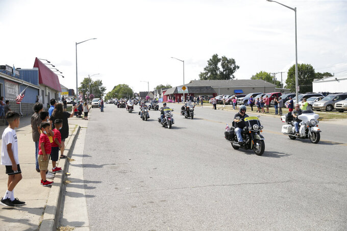 """Motorcycles drive along Burlington Avenue during the funeral procession for Marine Cpl. Humberto """"Bert"""" Sanchez, Tuesday, Sept. 14, 2021 in Logansport, Ind. Sanchez was one of 13 U.S. service members to die in an explosion during evacuation efforts in Afghanistan. (Nikos Frazier/Journal & Courier via AP)"""