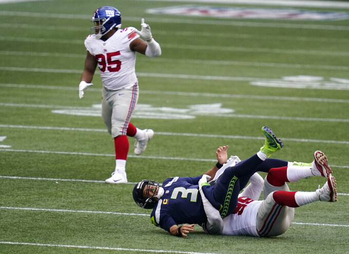 Seattle Seahawks quarterback Russell Wilson (3) is sacked by New York Giants defensive end Leonard Williams, right, during the first half of an NFL football game, Sunday, Dec. 6, 2020, in Seattle. (AP Photo/Elaine Thompson)