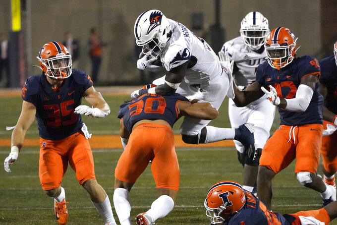 UTSA running back Sincere McCormick, top center, is upended by Illinois defensive back Sydney Brown (30) during the first half of an NCAA college football game Saturday, Sept. 4, 2021, in Champaign, Ill. (AP Photo/Charles Rex Arbogast)