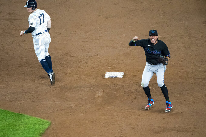 Miami Marlins shortstop Miguel Rojas, right, celebrates after throwing to first for the final out to clinch a playoff berth after the tenth inning of a baseball game against the New York Yankees at Yankee Stadium, Friday, Sept. 25, 2020, in New York. Yankees' Clint Frazier, left, looks back toward first base. (AP Photo/Corey Sipkin)