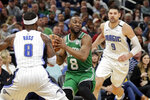 Boston Celtics guard Kemba Walker, center, looks to pass the ball as he is defended by Orlando Magic guard Terrence Ross, left, and center Nikola Vucevic (9) during the second half of an NBA basketball game, Friday, Jan. 24, 2020, in Orlando, Fla. (AP Photo/John Raoux)