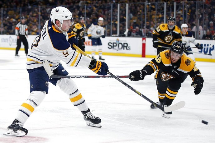 Buffalo Sabres' Jack Eichel (9) shoots past Boston Bruins' Matt Grzelcyk (48) to score against Tuukka Rask during the third period of an NHL hockey game in Boston, Sunday, Dec. 16, 2018. (AP Photo/Michael Dwyer)