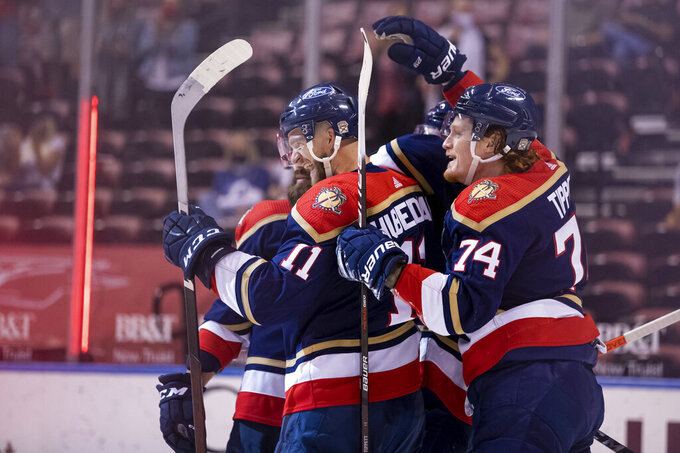 Florida Panthers left wing Jonathan Huberdeau (11) celebrates with right wing Owen Tippett (74) after scoring a goal during the second period of an NHL hockey game against the Tampa Bay Lightning, Saturday, May 8, 2021, in Sunrise, Fla. (AP Photo/Mary Holt)