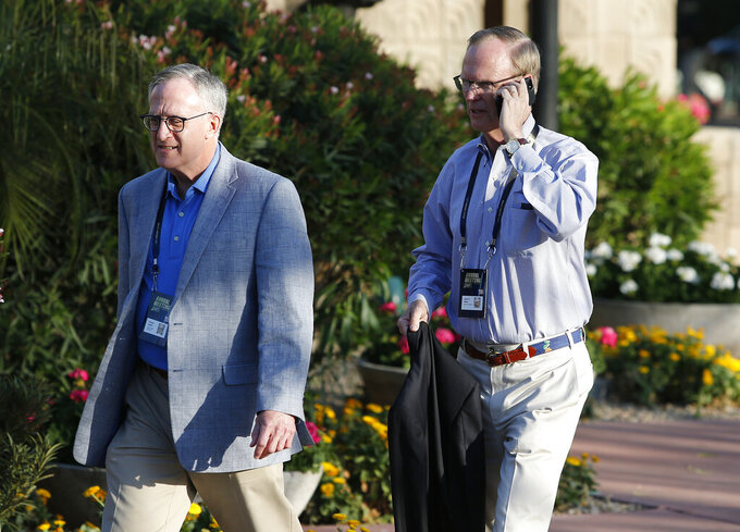 New York Giants football team president, CEO and co-owner John K. Mara, right, talks on his phone as he walks with the team's general council and senior vice president William Heller to a meeting during the annual NFL owners meetings, Sunday, March 24, 2019, in Phoenix. (AP Photo/Ralph Freso)