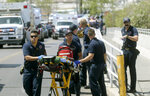 FILE - In this Aug. 3, 2019 file photo, El Paso Fire Medical personnel arrive at the scene of a shooting at a Walmart near the Cielo Vista Mall in El Paso, Texas. The FBI has labeled two of those attacks, at the Texas Walmart and California food festival, as domestic terrorism — acts meant to intimidate or coerce a civilian population and affect government policy. But the bureau hasn't gone that far with a shooting at an Ohio entertainment district. (Mark Lambie/The El Paso Times via AP, File)