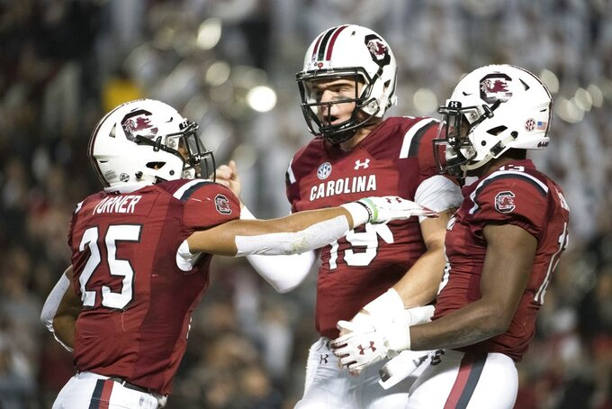 South Carolina quarterback Jake Bentley (19), AJ Turner (25), and Shi Smith (13) celebrate a touchdown during the first half of an NCAA college football game Saturday, Nov. 17, 2018, in Columbia, S.C. (AP Photo/Sean Rayford)