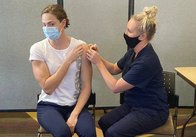 Swimmer Cate Campbell receives a Pfizer COVID-19 vaccination at the Queensland Academy of Sport in Brisbane, Australia, Monday, May 10, 2021. The Australian government announced after a special National Cabinet meeting that Olympic participants would be vaccinated under a priority group which includes health-care workers, Indigenous people aged over 55 and people older than 70. (AP Photo/John Pye)