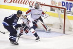 Winnipeg Jets' Tyler Myers (57) scores on Washington Capitals goaltender Braden Holtby (70) with Dmitry Orlov (9) in front of the net during overtime of an NHL hockey game Tuesday, Feb. 13, 2018, in Winnipeg, Manitoba. (Trevor Hagan/The Canadian Press via AP)
