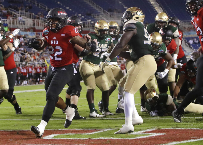 Northern Illinois running back Tre Harbison (22) runs past UAB linebacker Fitzgerald Mofor, right, to score a touchdown during the first half of the Boca Raton Bowl NCAA college football game, Tuesday, Dec. 18, 2018, in Boca Raton, Fla. (AP Photo/Lynne Sladky)