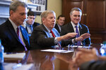 FILE- In this Feb. 14, 2019, file photo, Sen. Johnny Isakson, R-Ga., flanked by Rep. Buddy Carter R-Ga., left, and Sen. David Perdue, R-Ga., right, leads a meeting on Capitol Hill in Washington. Sen. Isakson announced on Wednesday, Aug. 28, 2019, that he will retire at the end of 2019, citing