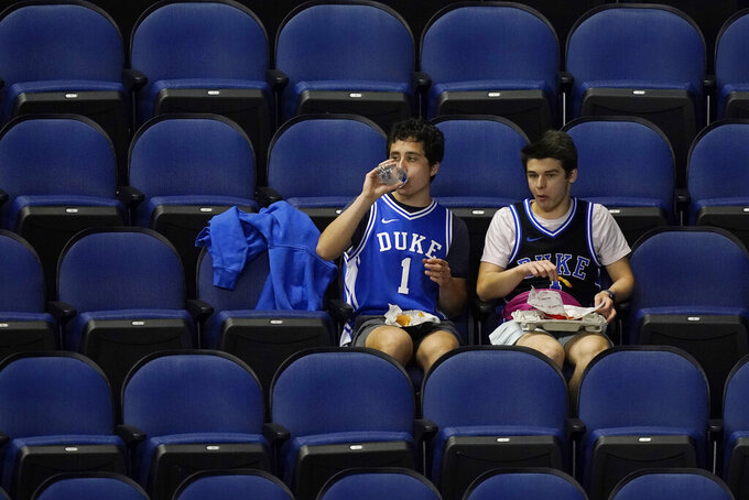 Duke fans watch the action during the second half of the Duke Boston College NCAA college basketball game in the first round of the Atlantic Coast Conference tournament in Greensboro, N.C., Tuesday, March 9, 2021. (AP Photo/Gerry Broome)