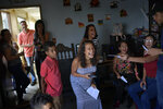 Ada Mendoza, 24, smiles during a game of riddles during her baby shower at her parents' apartment in the Catia neighborhood of Caracas, Venezuela, Saturday, Sept. 5, 2020. Mendoza has carried her baby amidst the coronavirus pandemic that has disrupted the lives of millions of Venezuelans, who since March 16th are still subject to a severe quarantine. (AP Photo/Matias Delacroix)