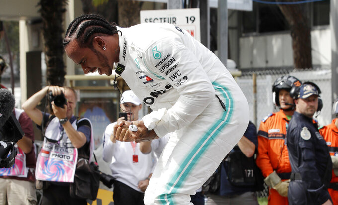 Mercedes driver Lewis Hamilton of Britain celebrates after he clocked the fastest time during the qualifying session at the Monaco racetrack, in Monaco, Saturday, May 25, 2019. The Formula one race will be held on Sunday. (AP Photo/Luca Bruno)