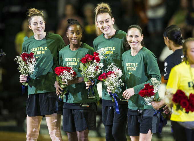 Seattle Storm's Katie Lou Samuelson, Jewell Loyd, Breanna Stewart and Sue Bird receive flowers to congratulate them on making the 2021 Team USA Women's Basketball team on Sunday, July 11, 2021 in Everett, Wash. (Olivia Vanni/The Herald via AP)