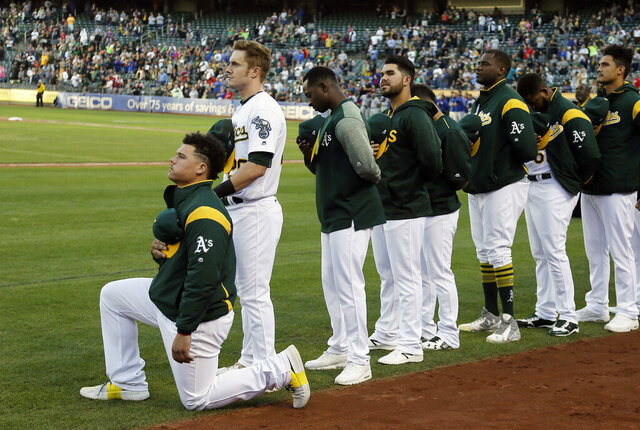 FILE - In this Sept. 23, 2017, file photo, Oakland Athletics catcher Bruce Maxwell kneels during the national anthem before the team's baseball game against the Texas Rangers in Oakland, Calif. Maxwell is the only major leaguer to take a knee during the playing of
