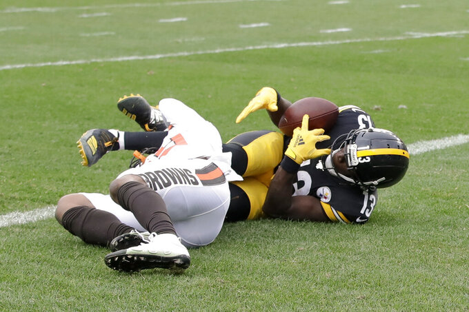 Pittsburgh Steelers wide receiver James Washington (13) grabs for the ball as he tries for a catch over Cleveland Browns defensive back Sheldrick Redwine (29) during the first half of an NFL football game, Sunday, Dec. 1, 2019, in Pittsburgh. The play was ruled a catch for a touchdown. (AP Photo/Gene J. Puskar)