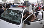 An investigator examines a damaged police vehicle at the site of hand grenade attack in Peshawar, Pakistan, Friday, July 30, 2021. Attackers threw a hand grenade at a police van in Pakistan's northwestern city of Peshawar on Friday, killing and wounding policemen before fleeing the scene, police said. (AP Photo/Muhammad Sajjad)