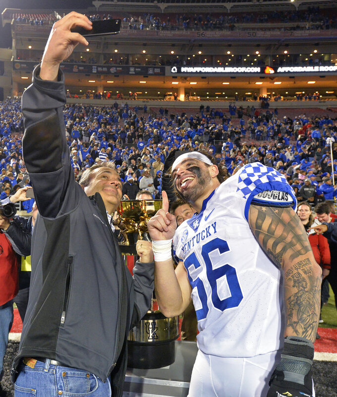 Kentucky Gov. Matt Bevin, left, takes a selfie with Kentucky linebacker Kash Daniel (56) in front of the Governor's Cup following Kentucky's 56-10 victory over Louisville in an NCAA college football game, in Louisville, Ky., Saturday, Nov. 24, 2018.  (AP Photo/Timothy D. Easley)