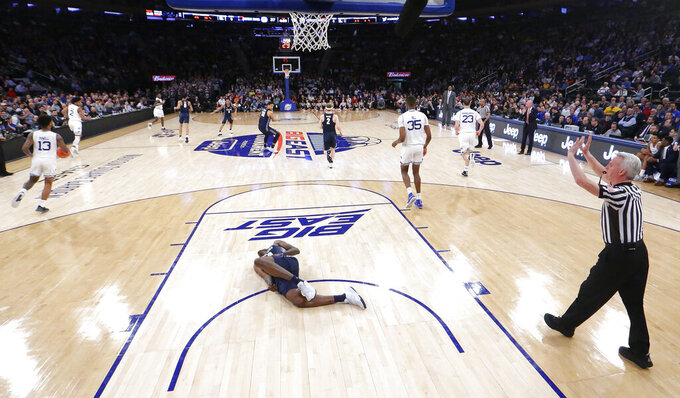 Georgetown forward Josh LeBlanc lies on the court after taking a fall on a play against Seton Hall during the first half of an NCAA college basketball game in the Big East men's tournament, Thursday, March 14, 2019, in New York. Seton Hall won 73-57. (AP Photo/Julio Cortez)
