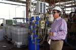 Derek Benson, chief operating officer of EnergySource Minerals, stands in front of the Iliad, integrated lithium absorption and desorption machine, used to separate brine extracted from the ground into lithium, Friday, July 16, 2021, in Calipatria, Calif. Benson says the company has extracted lithium there on a small scale since 2016 and plans to build a much larger addition for mineral extraction. (AP Photo/Marcio Jose Sanchez)