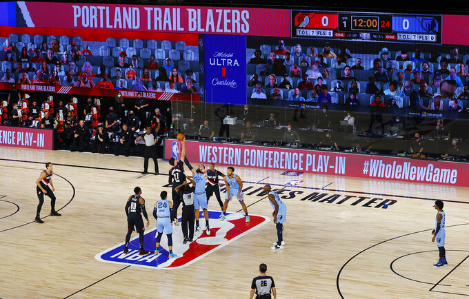 FILE - In this Aug. 15, 2020, file photo, Portland Trail Blazers' Jusuf Nurkic (27) and Memphis Grizzlies' Jonas Valanciunas (17) reach for the opening top in an NBA basketball play-in game in Lake Buena Vista, Fla.  The 2020-21 NBA schedule will feature a play-in tournament and an NBA Finals that could run all the way until July 22 — keeping some players from competing in the Olympics. (Kevin C. Cox/Pool Photo via AP, File)